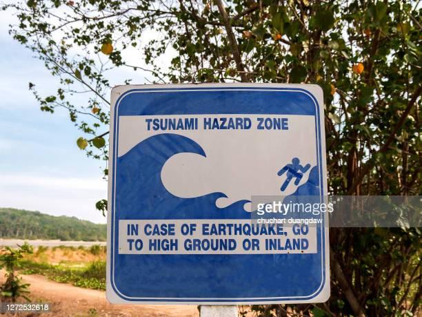 tsunami evacuation route sign on the beach, phuket, thailand - tsunami stock pictures, royalty-free photos & images