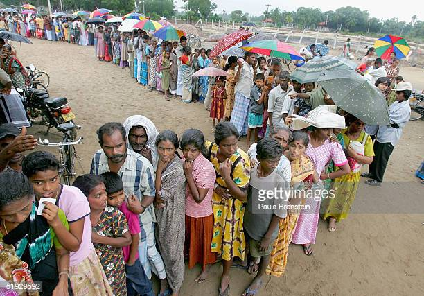 Tsunami refugees wait in the rain to receive nonfood relief item packages during a UNHCR distribution for 688 families January 92004 in a welfare...