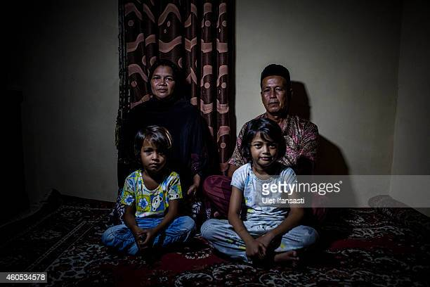 Tsunami survivor Sanusi and his wife Hasrati sits inside their house with their daughter at Lamtutui village on December 15 2014 in Banda Aceh...