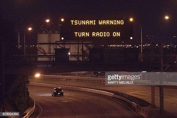 A tsunami warning alert is seen on a notice board above State Highway 1 in Wellington early on November 14 2016 following an earthquake centred some...