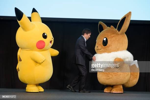 Tsunekazu Ishihara chief executive officer of Pokemon Co appears on the stage with Pokomon characters Pikachu left and Eevee during a Pokemon news...