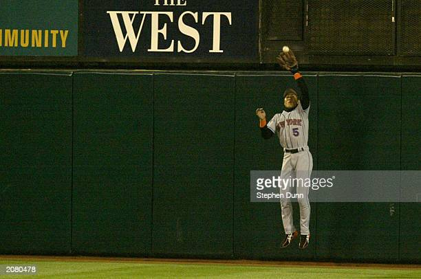 Tsuyoshi Shinjo center fielder for the New York Mets makes the catch at the wall on a long drive by Tim Salmon of the Anaheim Angels in the seventh...