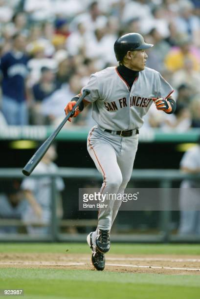 Tsuyoshi Shinjo of the San Francisco Giants watches his first inning home run clear the fence against the Colorado Rockies at Coors Field in Denver...