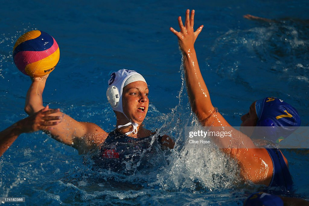 Tóth Ildikó of Hungary passes the ball under pressure from Melani Dias of Brazil compete in the Women's Water Polo first preliminary round match between Hungary and Brazil during Day Two of the 15th FINA World Championships at Piscines Bernat Picornell on July 21, 2013 in Barcelona, Spain.