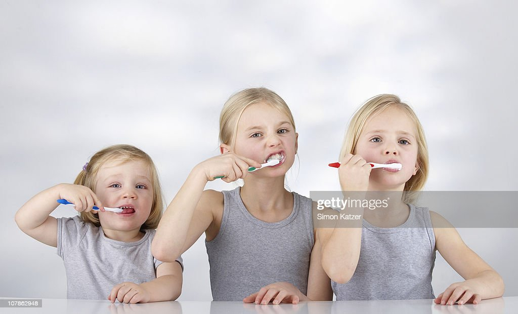 Tthree children brushing their teeth : Stock Photo