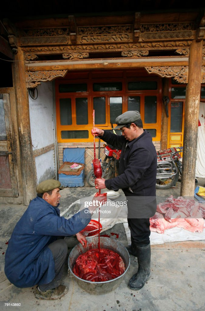 Tu ethnic villagers make blood sausages after slaughtering a pig at the Wushi Village on January 21, 2008 in Huzhu County of Qinghai Province, China. In countryside of Qinghai Province, many villages of the Han, Tu and other ethnic groups have keeped the tradition of slaughtering pigs in the twelfth month of the lunar year, to prepare pork for the upcoming Chinese New Year, or Spring Festival.