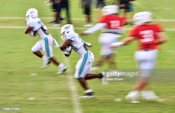 Tua Tagovailoa hands the ball to Malcolm Perry while Josh Rosen hands the ball to Matt Breida of the Miami Dolphins during training camp at Baptist...