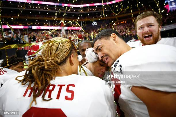 Tua Tagovailoa of the Alabama Crimson Tide celebrates with Jalen Hurts after beating the Georgia Bulldogs in overtime to win the CFP National...