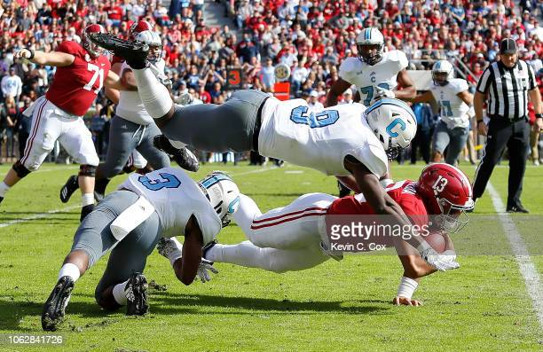 Tua Tagovailoa of the Alabama Crimson Tide dives for more yardage against Joshua Bowers and Willie Eubanks III of the Citadel Bulldogs at...