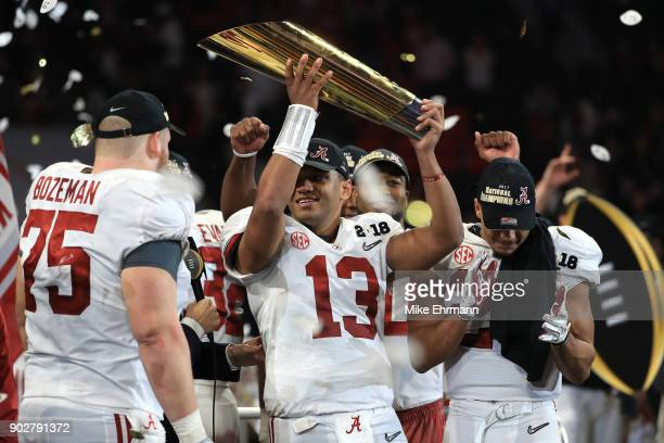 Tua Tagovailoa of the Alabama Crimson Tide holds the trophy while celebrating with his team after defeating the Georgia Bulldogs in overtime to win...