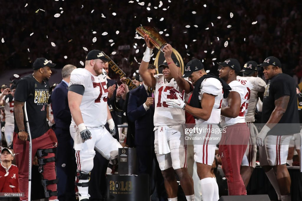 Tua Tagovailoa #13 of the Alabama Crimson Tide holds the trophy while celebrating with his team after defeating the Georgia Bulldogs in overtime to win the CFP National Championship presented by AT&T at Mercedes-Benz Stadium on January 8, 2018 in Atlanta, Georgia. Alabama won 26-23.