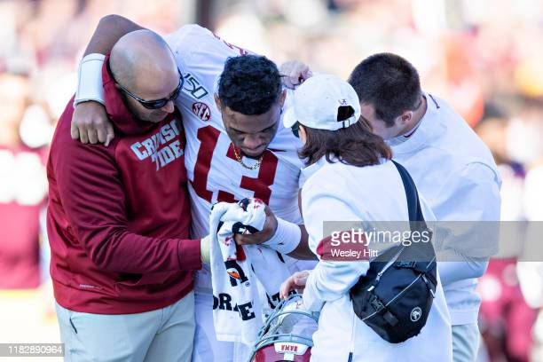 Tua Tagovailoa of the Alabama Crimson Tide is helped off the field after being injured on a play in the first half of a game against the Mississippi...