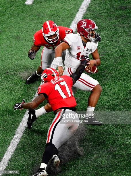 Tua Tagovailoa of the Alabama Crimson Tide is pursued by Reggie Carter and Davin Bellamy of the Georgia Bulldogs in the CFP National Championship...
