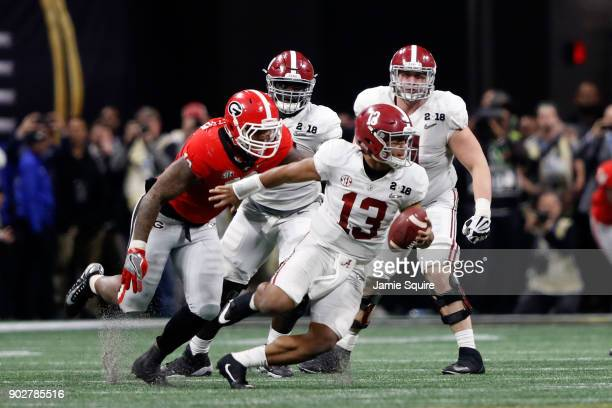 Tua Tagovailoa of the Alabama Crimson Tide is sacked by Jonathan Ledbetter of the Georgia Bulldogs during overtime in the CFP National Championship...