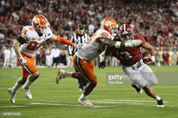 Tua Tagovailoa of the Alabama Crimson Tide is tackled by Clelin Ferrell of the Clemson Tigers in the CFP National Championship presented by ATT at...
