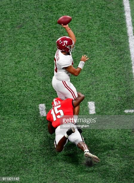 Tua Tagovailoa of the Alabama Crimson Tide passes despite pressure by D'Andre Walker of the Georgia Bulldogs in the CFP National Championship...