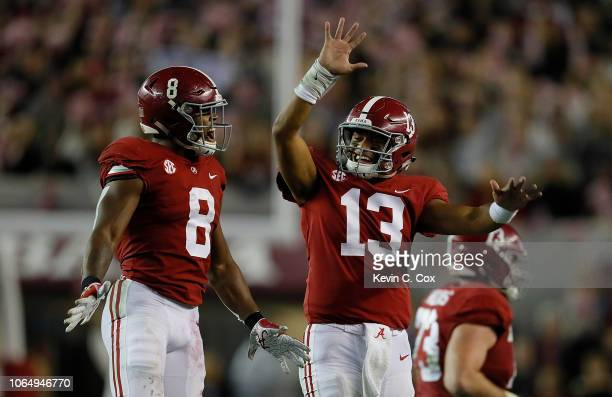 Tua Tagovailoa of the Alabama Crimson Tide reacts after passing for a touchdown to DeVonta Smith against the Auburn Tigers with Josh Jacobs at...
