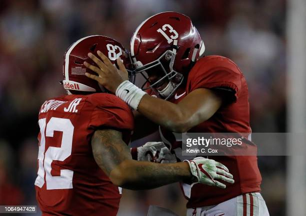 Tua Tagovailoa of the Alabama Crimson Tide reacts after passing for a touchdown to Henry Ruggs III against the Auburn Tigers with Irv Smith Jr #82 at...