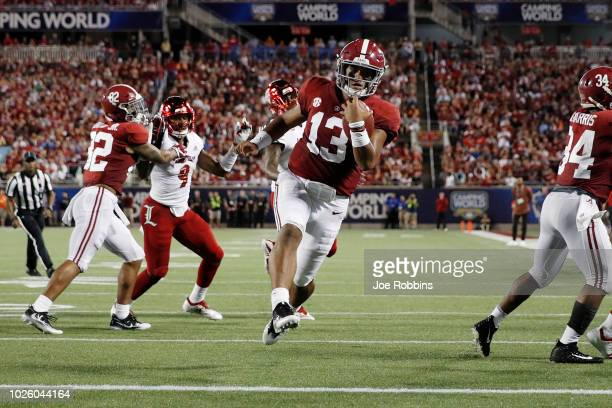 Tua Tagovailoa of the Alabama Crimson Tide runs for a nine-yard touchdown in the first quarter of the game against the Louisville Cardinals at...