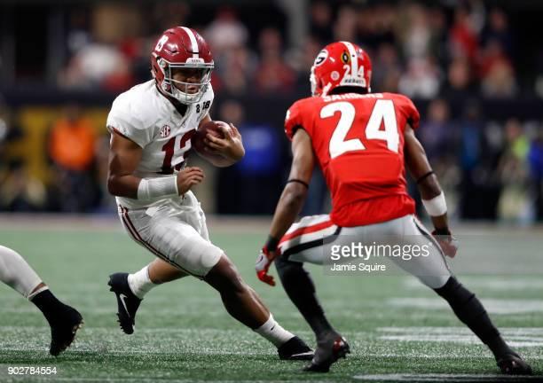 Tua Tagovailoa of the Alabama Crimson Tide runs the ball against Dominick Sanders of the Georgia Bulldogs during the second half in the CFP National...