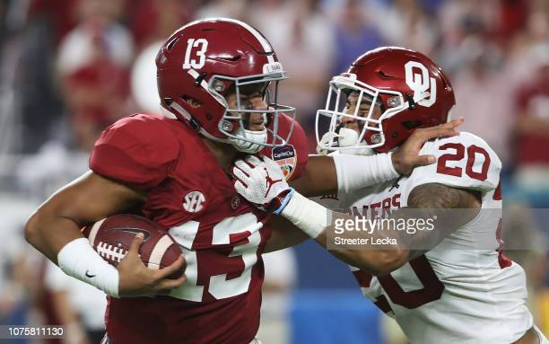 Tua Tagovailoa of the Alabama Crimson Tide stiff arms Tre Norwood of the Oklahoma Sooners in the first half during the College Football Playoff...