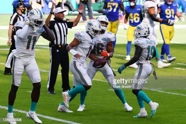 Tua Tagovailoa of the Miami Dolphins celebrates his first NFL touchdown on a three-yard pass to DeVante Parker against the Los Angeles Rams during...
