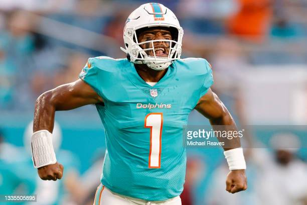 Tua Tagovailoa of the Miami Dolphins reacts to a touchdown run by Myles Gaskin against the Atlanta Falcons during a preseason game at Hard Rock...