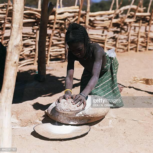 Tuareg girl grinding millet Iferouane oasis Air mountains Agadez region Niger
