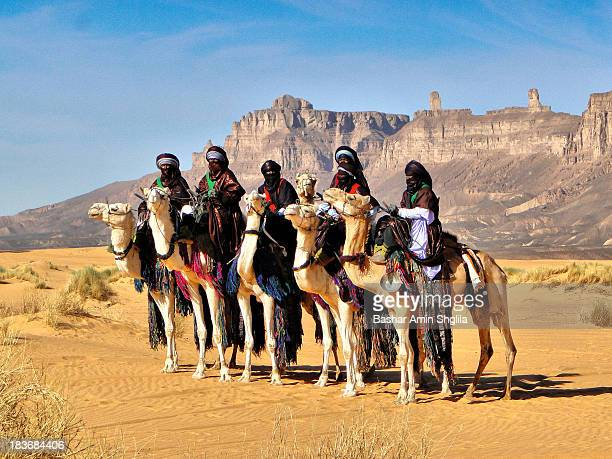 CONTENT] Tuareg knights riding their camels and standing in front of the famous mountains called Kaf Ejjnoon at Ghat desert in Libya