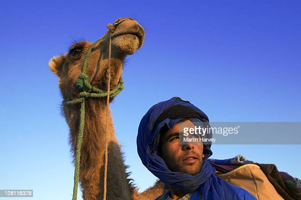 Tuareg man dressed in traditional blue robe with camel in the Erg Chebbi area. Sahara desert. Morocco