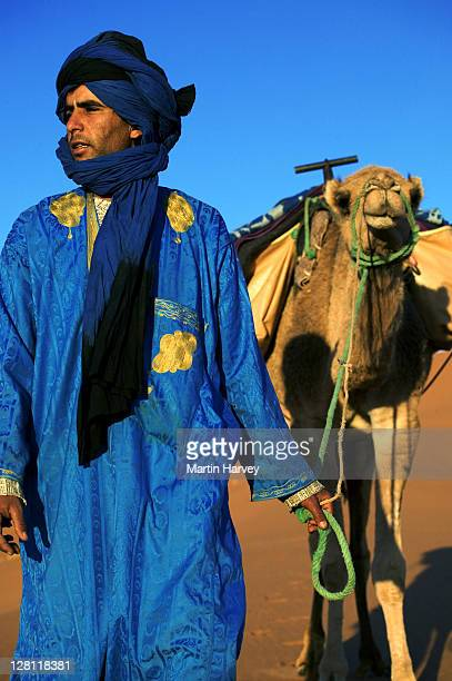 tuareg man dressed in traditional blue robe with camel in the erg chebbi area. sahara desert. morocco - touareg photos et images de collection