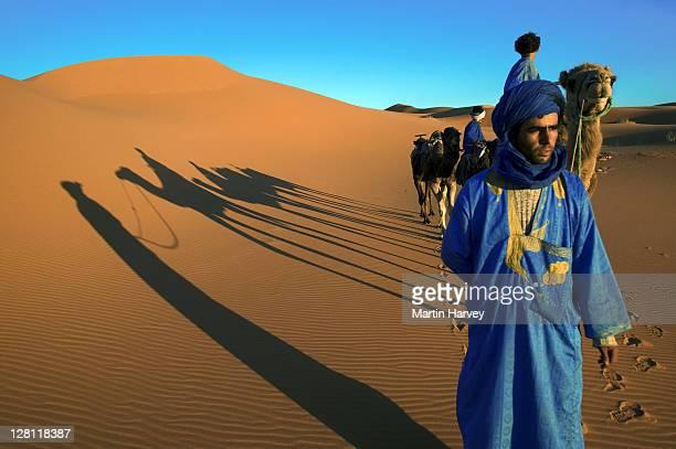 tuareg man dressed in traditional blue robe with camel in the erg chebbi area. sahara desert. morocco - nordafrika stock-fotos und bilder