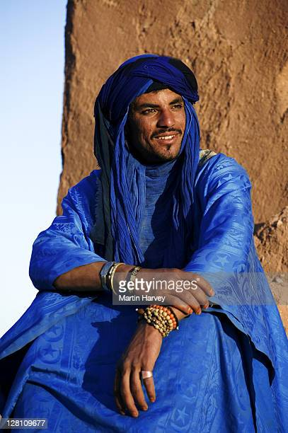 Tuareg man, dressed in traditional clothing, with Ait Benhaddou Kasbah in the background. Near the town of Ouarzazate. Morocco