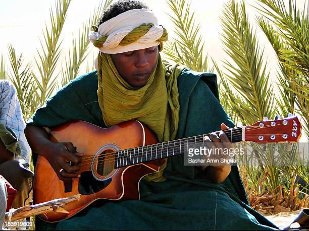 CONTENT] Tuareg Man playing a Guitar near of GaberOun Oasis at Libyan Desert