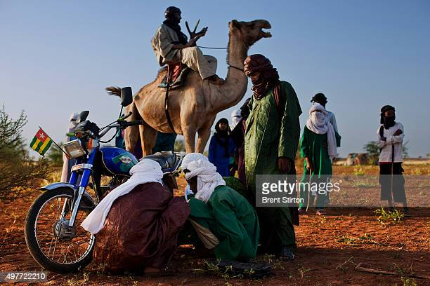 Tuareg men repair a small engined motorcycle in a Tuareg Nomad camp while a man on the more traditional camel looks on October 9 2009 in Ingal Niger...