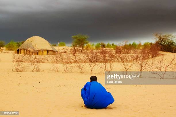 tuareg stalking at dark clouds - mali stock pictures, royalty-free photos & images