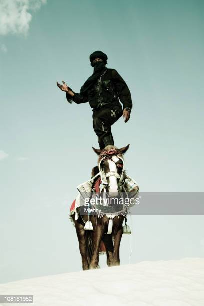 Tuareg Standing on Horse in Sand Dune