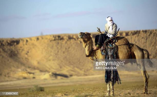 Tuareg tribesman rides a camel during a traditional ceremony in the Libyan desert in the western Awal region near the borders with Tunisia and...