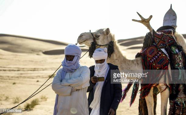 Tuareg tribesman uses his cell phone to film while attending a traditional ceremony in the Libyan desert in the western Awal region near the borders...