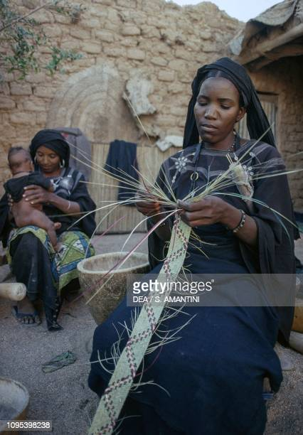 Tuareg woman making a straw ribbon, a woman with child in the background, Timia Oasis, Air and Tenere Nature Reserve , Niger.