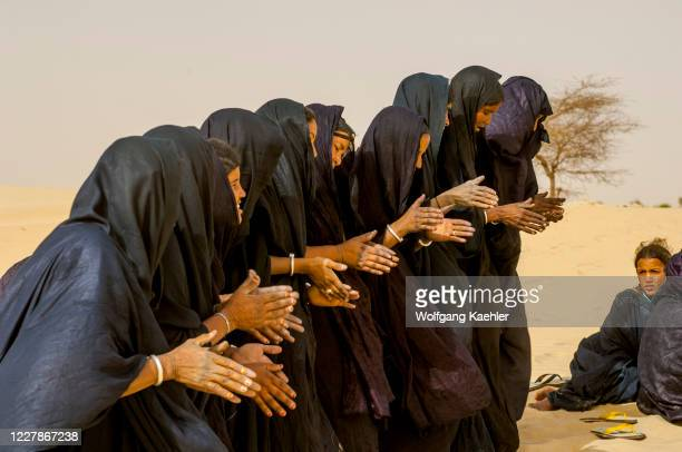 Tuareg women performing a traditional dance, clapping their hands, in the desert at the edge of Timbuktu, Mali, a city on the edge of the Sahara.