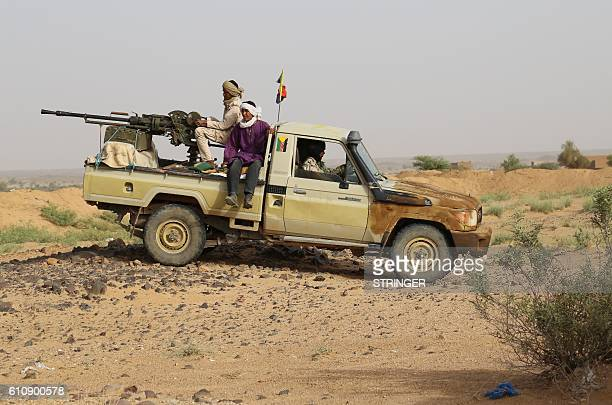 TOPSHOT Tuaregs fighters of the Coordination of Movements of the Azawad stand on a pick up truck with a machine gun near Kidal northern Mali on...
