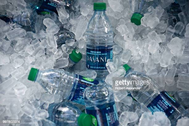 A tub filled with ice and plastic bottles of Dasani purified bottled water being given away at a Fourth of July holiday event in Santa Fe New Mexico...