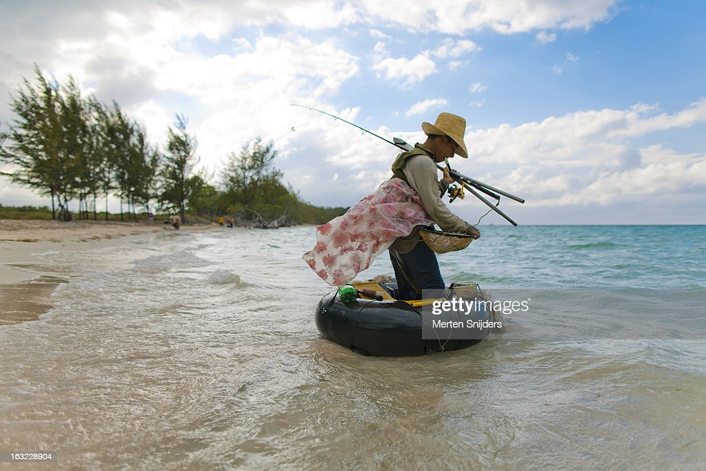 Tube fisherman with rods on beach : Stockfoto