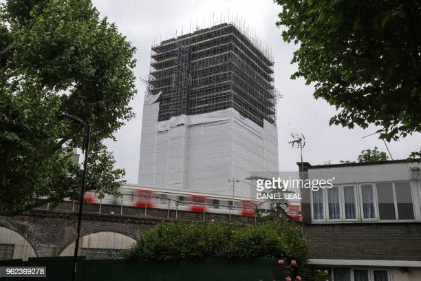 Tube train passes the burned-out shell of Grenfell Tower block in west London on May 25, 2018. - Fighting back tears, relatives of the victims of the...
