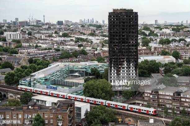 A tube train passes the remains of Grenfell Tower seen from a neighbouring tower block on June 26 2017 in London England 79 people have been...