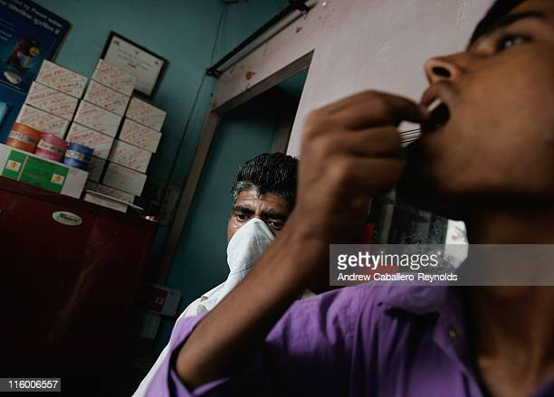 A tuberculosis patient looks on as another patient takes his medication at an operation ASHA treatment center on June 2 in New Delhi India NGOs such...