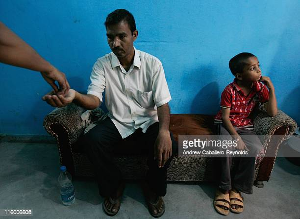 A tuberculosis patient receives his medication as a young TB patient waits for his dose at an operation ASHA treatment center on June 1 in New Delhi...
