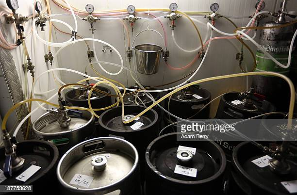 Tubes leading upstairs to beer taps are seen connected to kegs of beer in the cellar at Hops Barley brewery on November 12 2013 in Berlin Germany In...