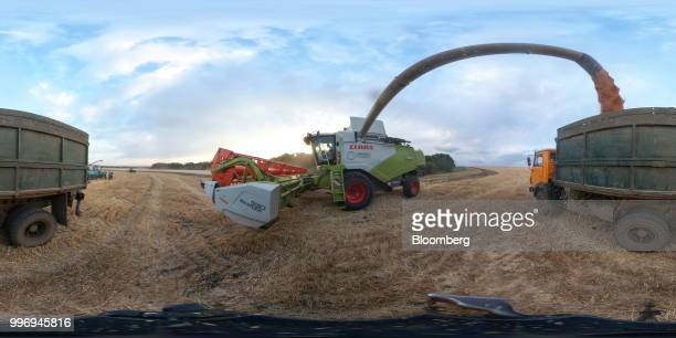 A Tucano combine harvester manufactured by Claas KGaA unloads harvested wheat grain into a truck during the summer harvest on a farm operated by Ros...